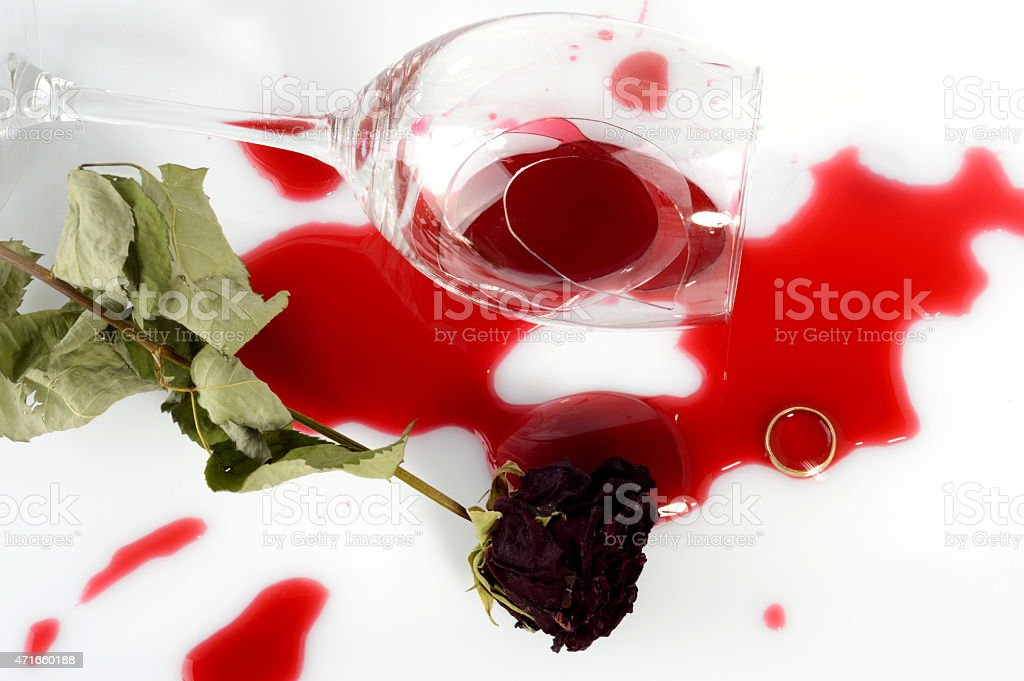 Broken glass, faded rose and a ring after an argument stock photo