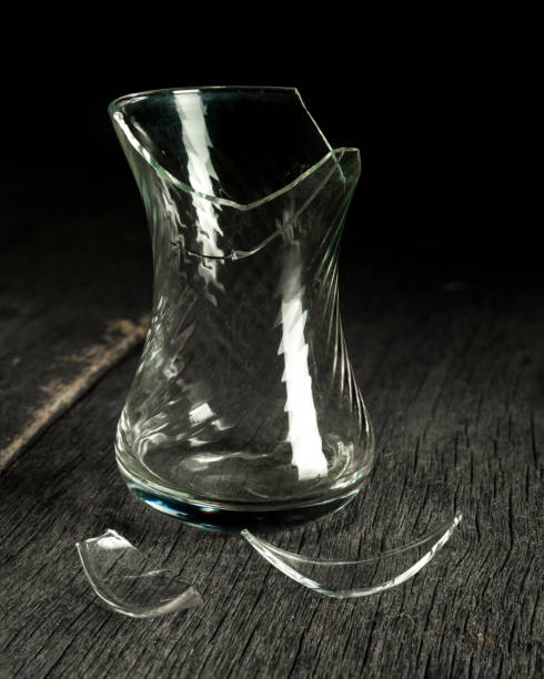 broken glass glass and shards on a gray wooden background low key stock photo