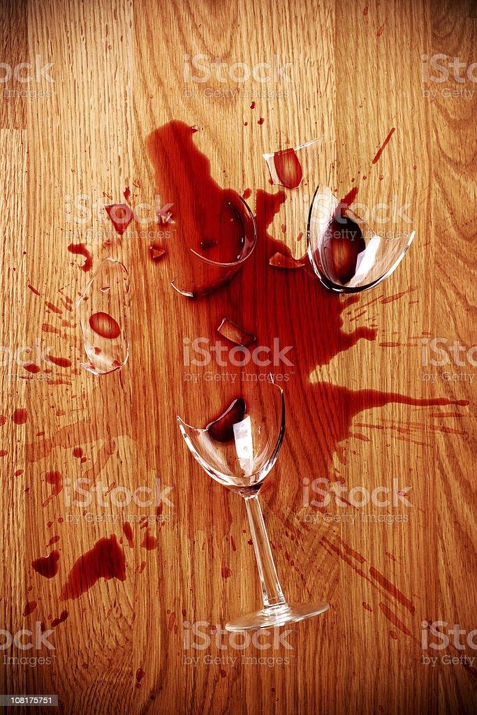 Broken Glass of Red Wine on Hardwood Floor stock photo