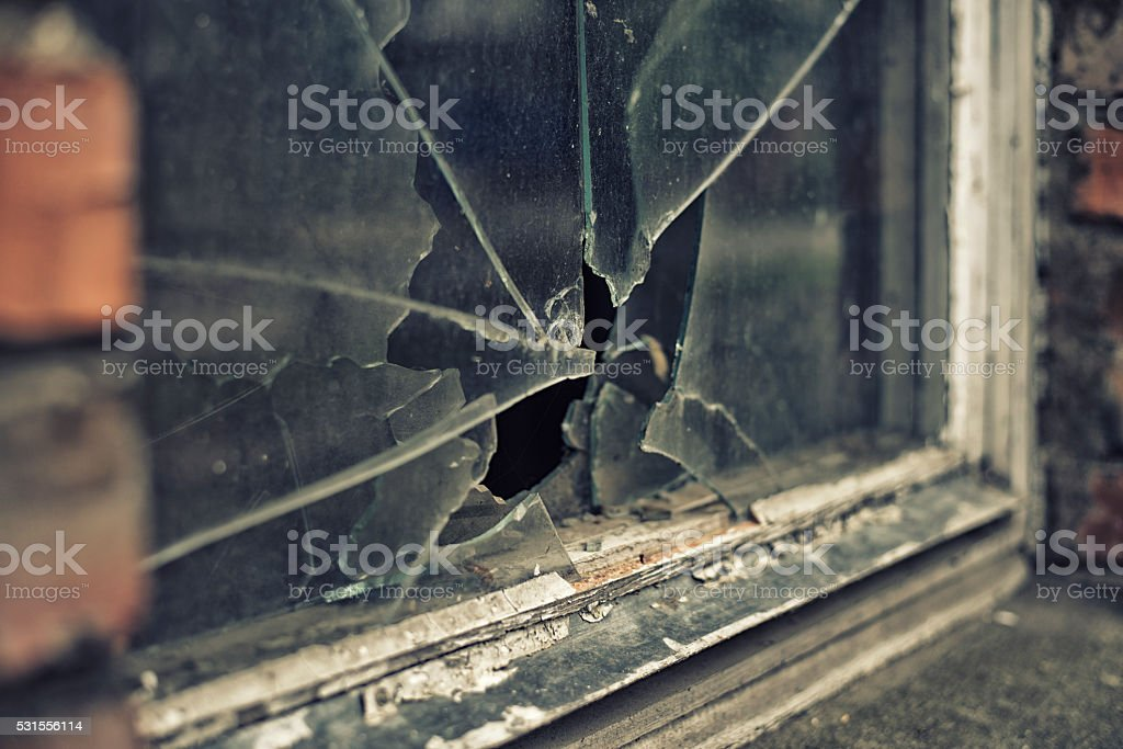 broken glass window reflecting clounding sky stock photo