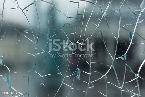 istock Broken glass with cracks with a blurred background of city streets 868260138