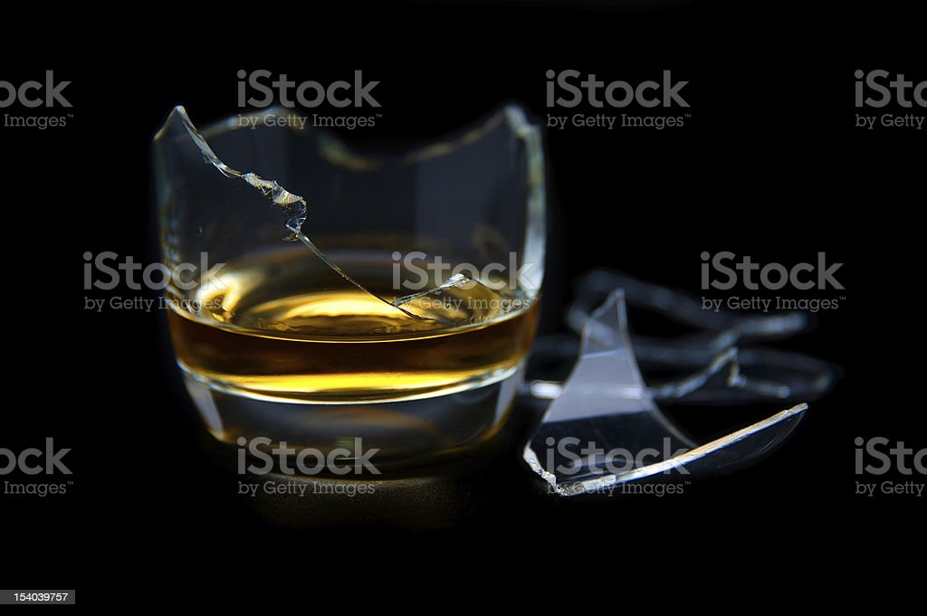 Broken glass with whisky stock photo