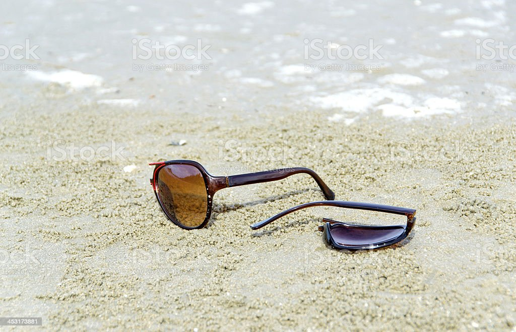 broken glasses on sand stock photo