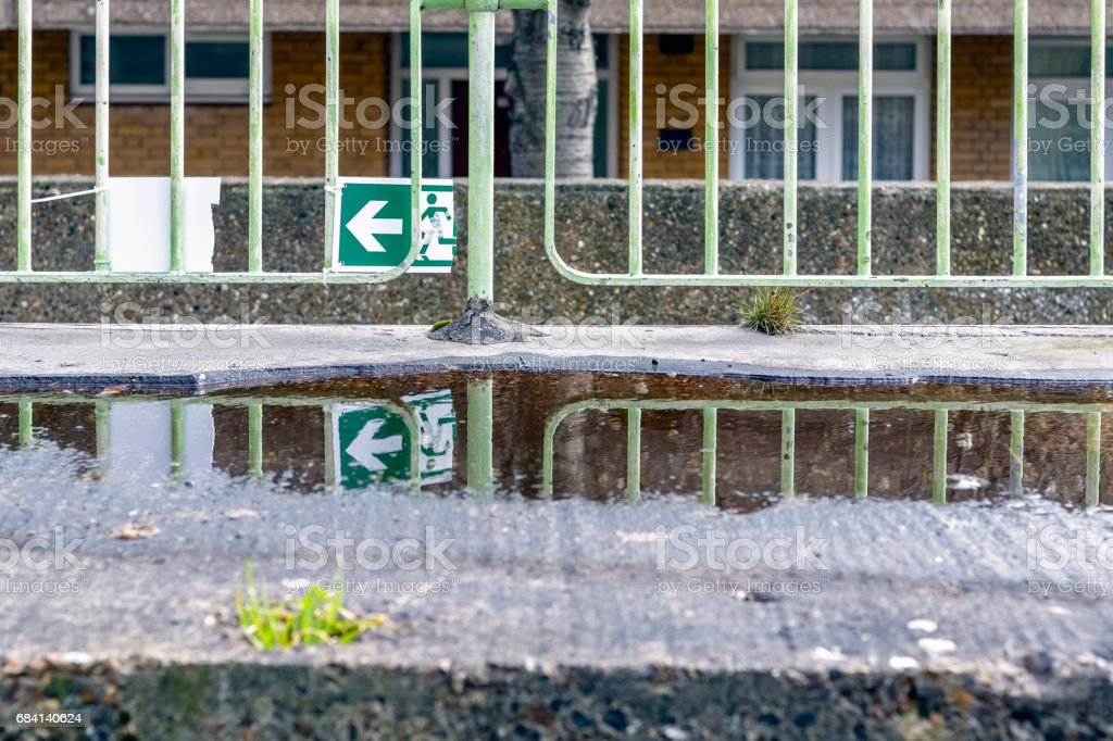 Broken green emergency exit sign and its reflection from a puddle foto stock royalty-free