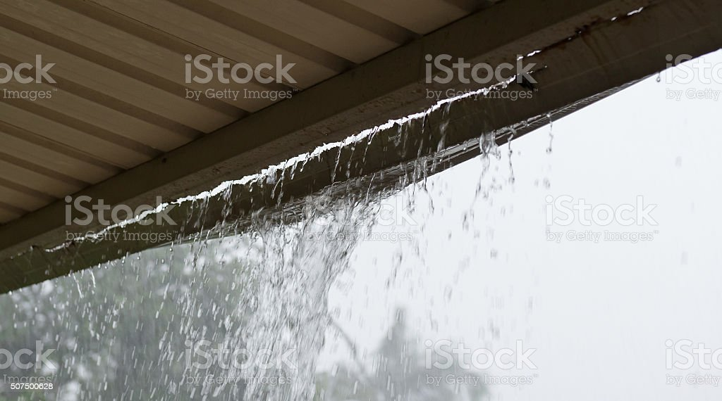 Broken Gutter with rain pouring through stock photo