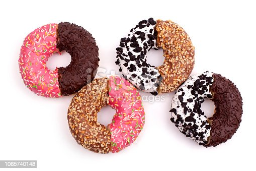 istock Broken halves of donuts on white background isolated top view 1065740148