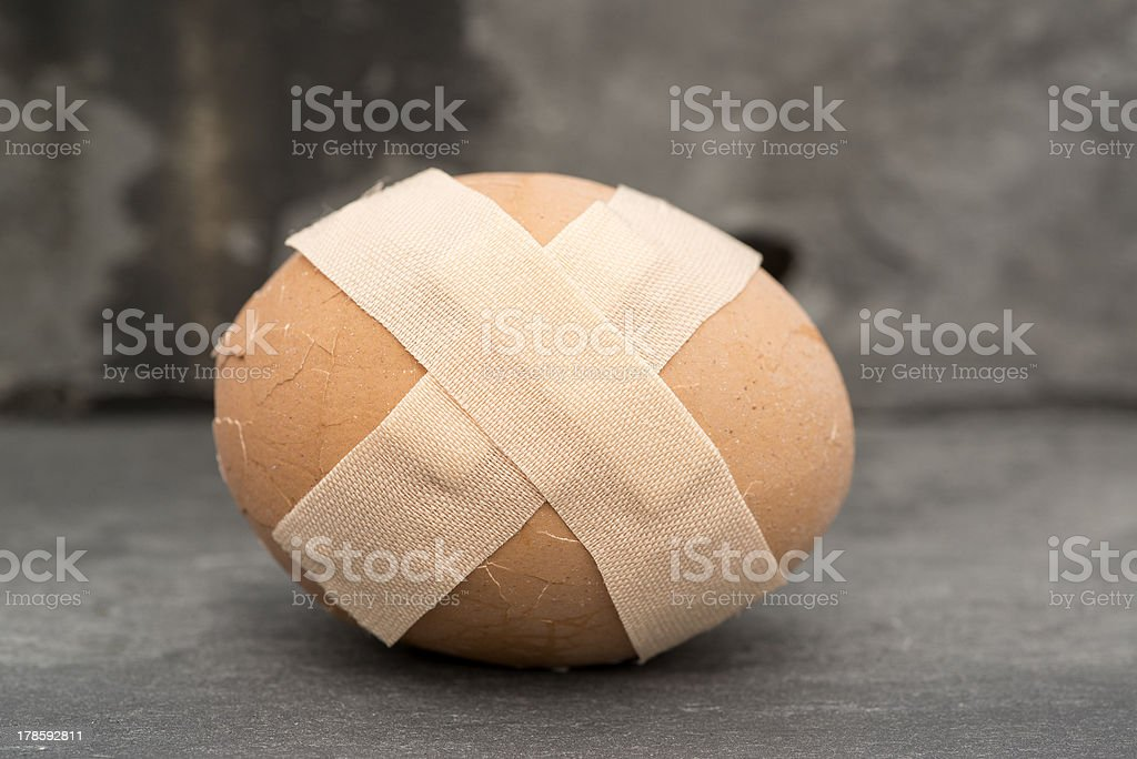 Broken healthcare concept image of plaster on egg royalty-free stock photo
