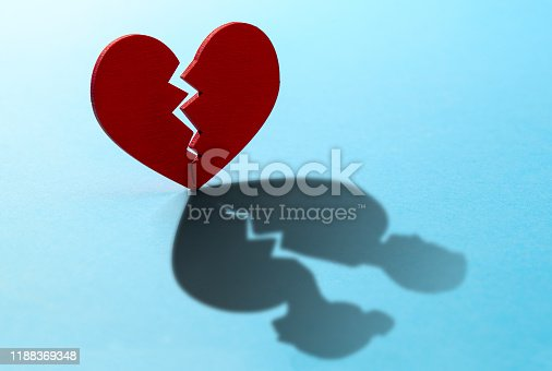 istock Broken heart. Crack in the red heart, Breaking the relationship. Shadow from the heart in the form of two figures of man and woman 1188369348