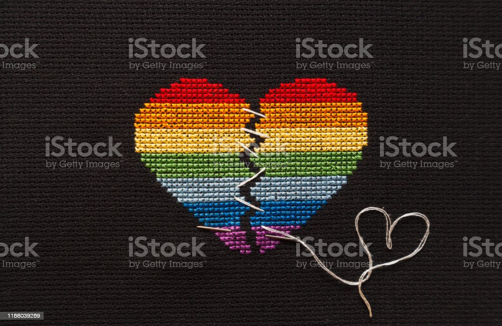 Broken heart embroidered on black cloth with rainbow threads. Heart...
