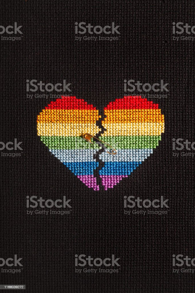 Broken heart embroidered on black cloth with rainbow threads. The...