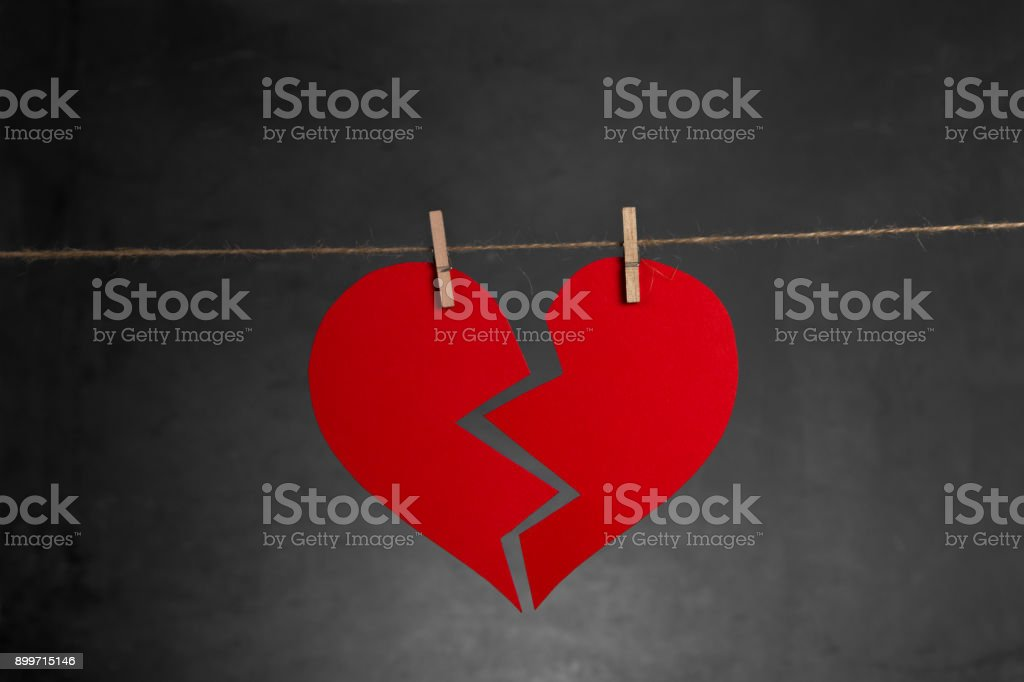 Broken Heart hanging on the rope on black background. Valentine\'s Day