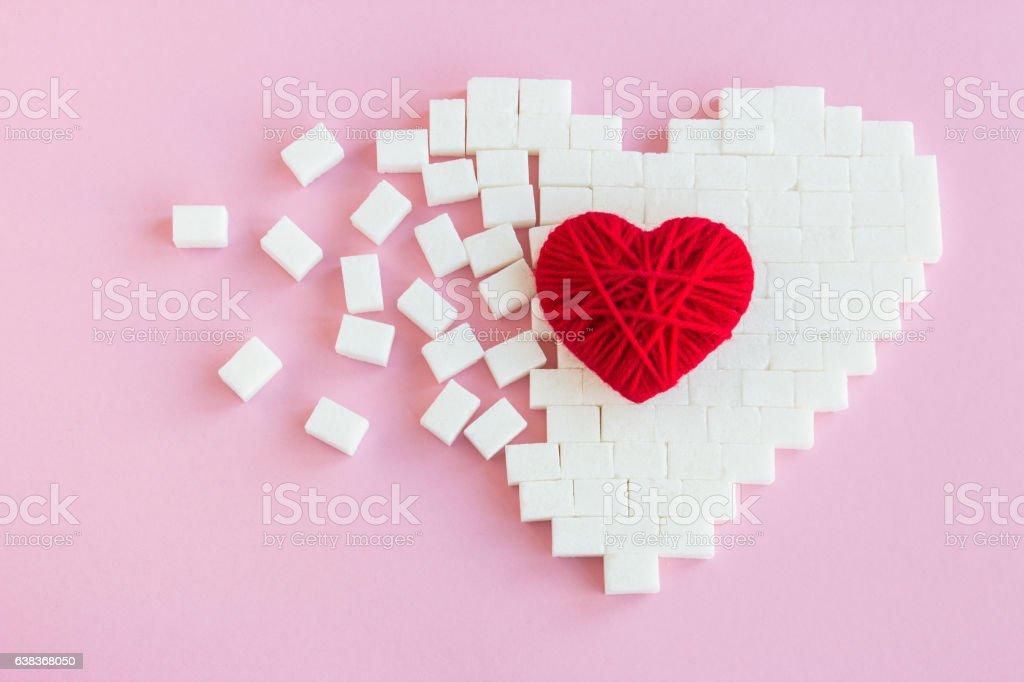 Broken heart made of sugar cubes stock photo