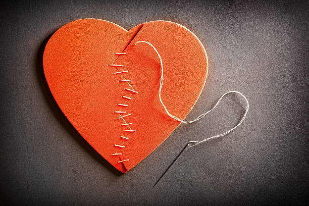 Broken Heart On The Mend A broken heart with a needle and thread stitching it back together. red broken heart sewn threads stock pictures, royalty-free photos & images