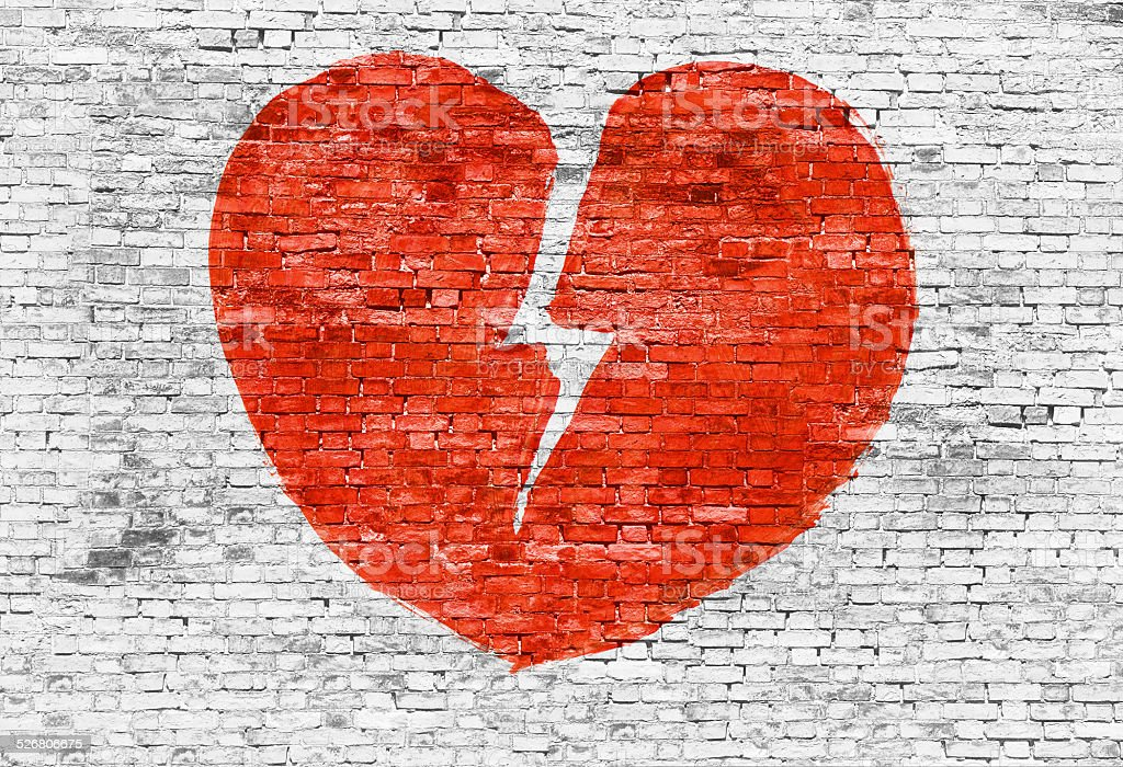 Broken heart painted on brick wall stock photo