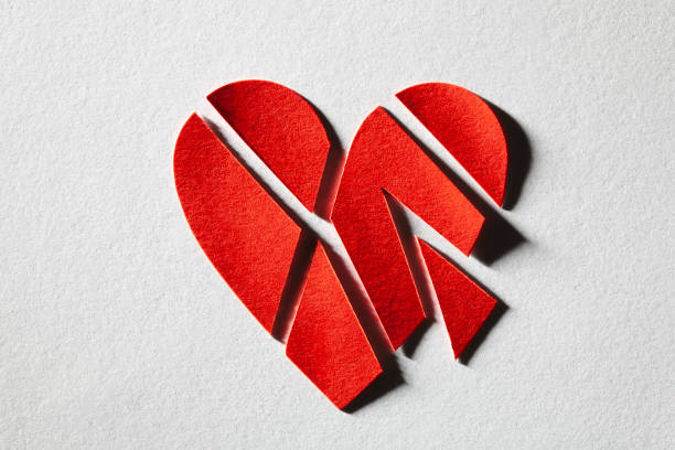 Broken heart. Red cut paper heart on a white background. stock photo