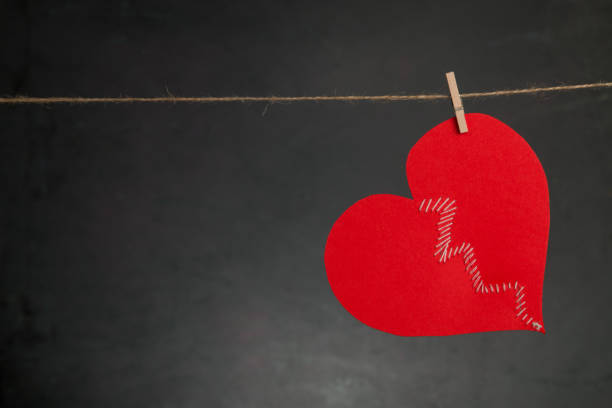 Broken Heart sewed up hanging on the rope on black background. Valentine's Day Broken Heart sewed up hanging on the rope on black background. Valentine's Day red broken heart sewn threads stock pictures, royalty-free photos & images