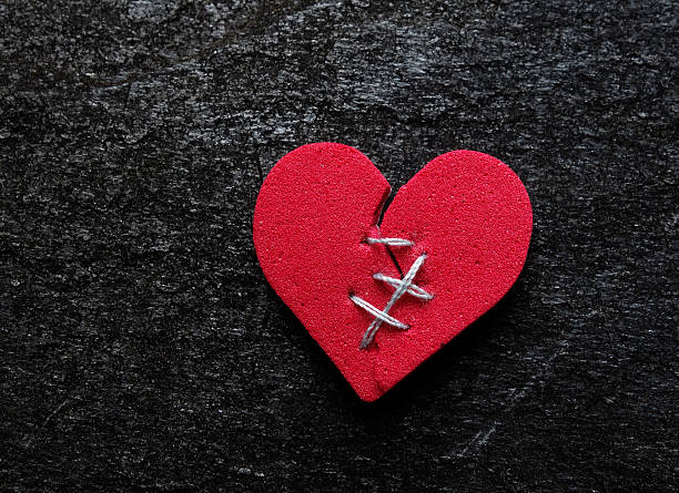 Broken hearted Red broken heart with thread stitches on dark background red broken heart sewn threads stock pictures, royalty-free photos & images