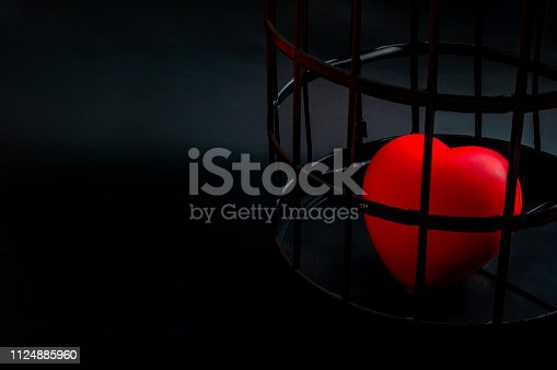 istock Broken hearts, loneliness and heartache concept with a lonely heart locked away in a black cage isolated on black background with copyspace 1124885960