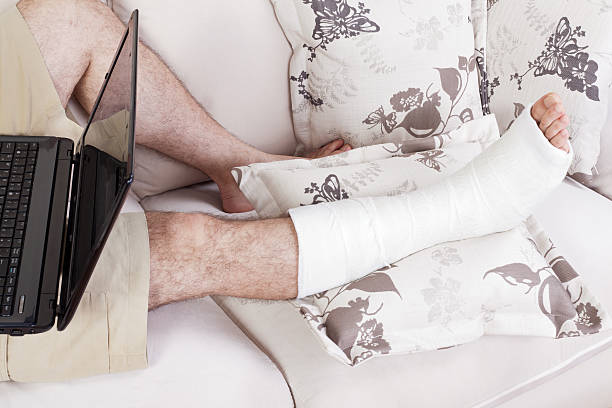 broken leg and working in home office - broken leg stock photos and pictures