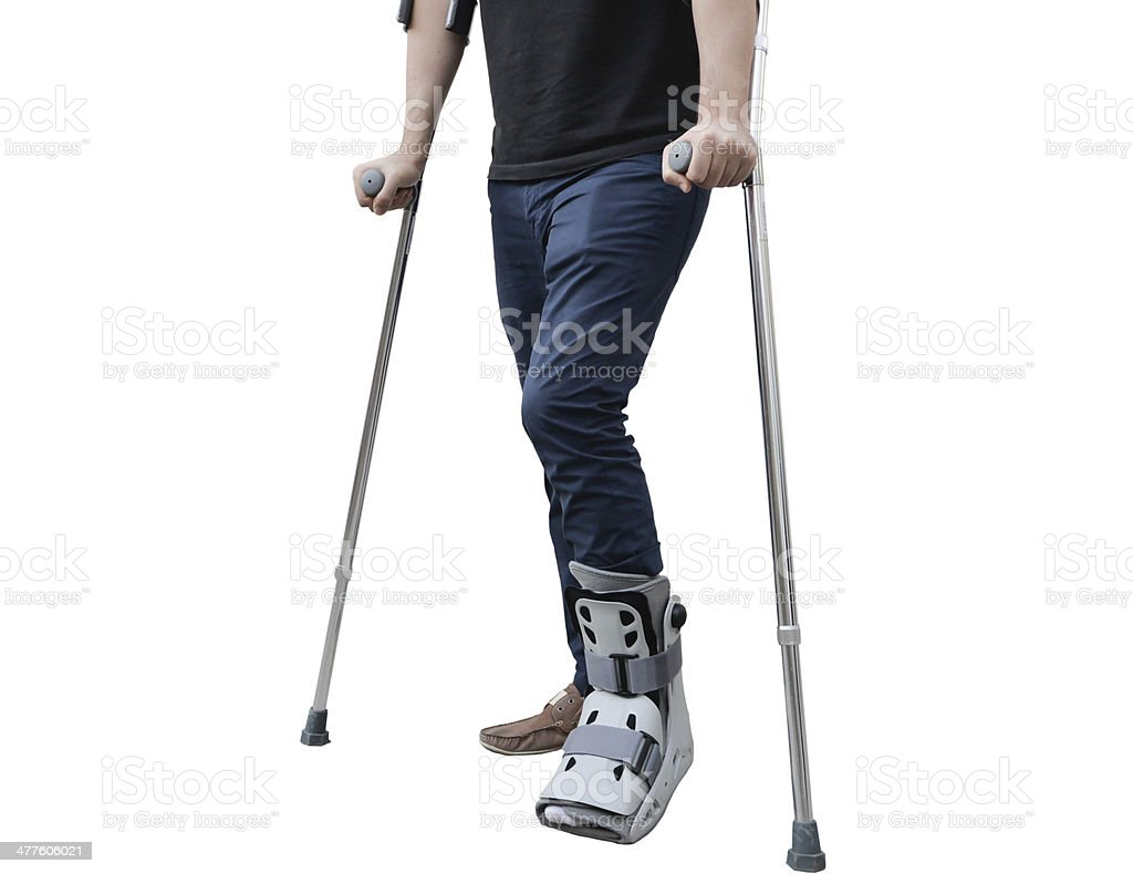 broken leg man wearing ankle support with walking crutches stock photo