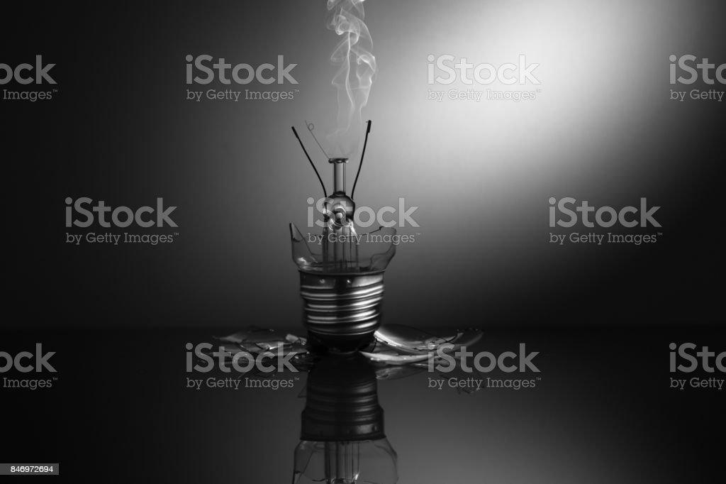 Broken light bulb smoking stock photo