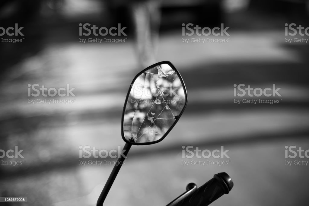 A broken looking mirror of a bike stock photo