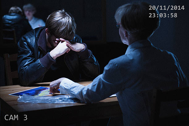 Broken man in interrogation room Broken man sitting in interrogation room with policewoman police interview stock pictures, royalty-free photos & images