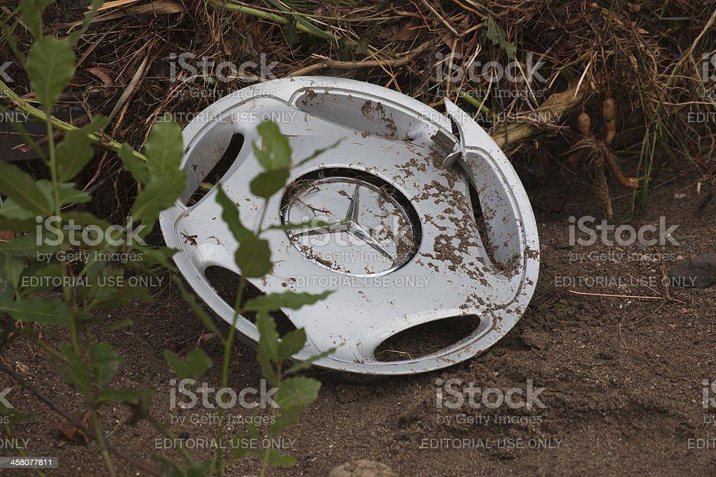 Broken Mercedes-Benz hubcap in mud stock photo