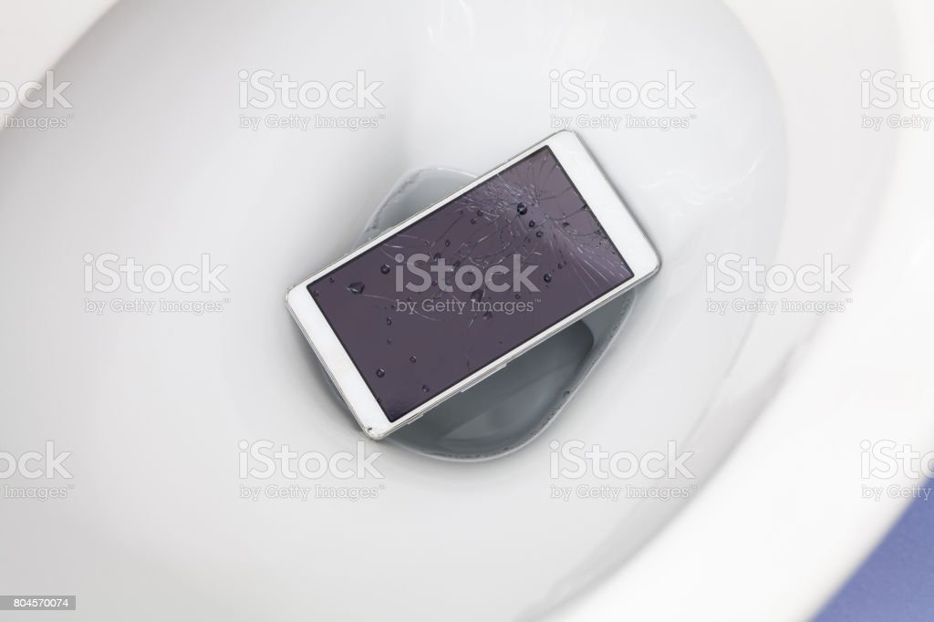 Broken mobile phone dropped into toilet bowl stock photo
