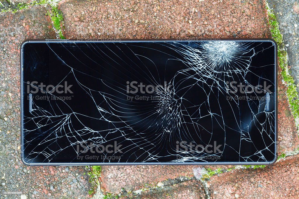 Broken mobile phone lying on pavement stock photo