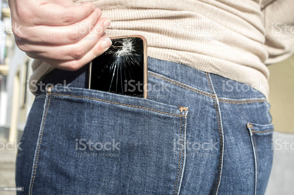 Broken mobile phone up from her pocket jeans pant after sitting over it stock photo