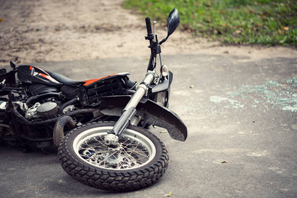 Broken motorcycle on the road after traffic incident stock photo