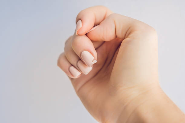 broken nail on a woman's hand with a manicure on a green background - fragility stock pictures, royalty-free photos & images
