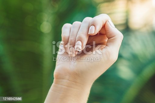 857308152 istock photo Broken nail on a woman's hand with a manicure on a green background 1216542586