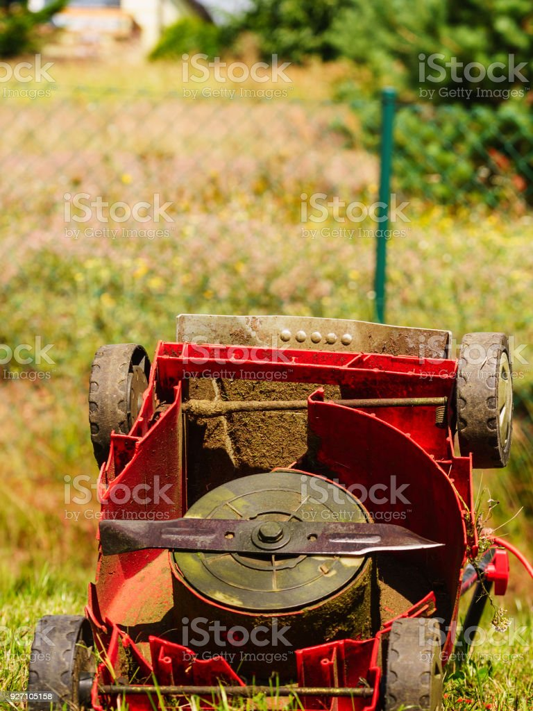 Broken old lawnmower in backyard grass stock photo