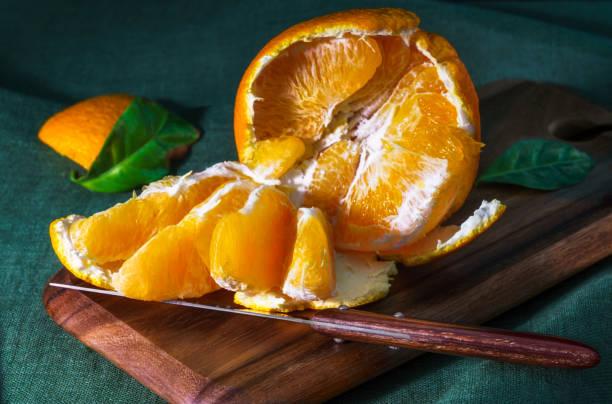 A broken orange on the kitchen Board stock photo