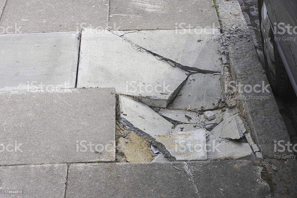 Broken pavement damage cracked paving stones next to kerb stock photo