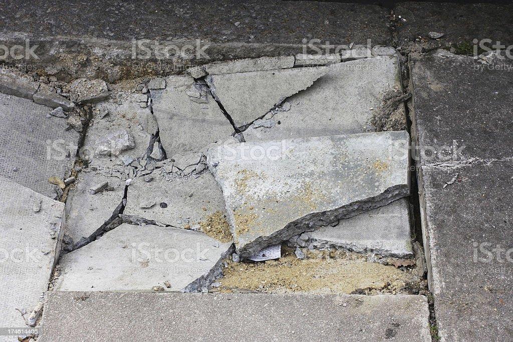 Broken pavement sidewalk damage cracked paving stones next to kerb stock photo
