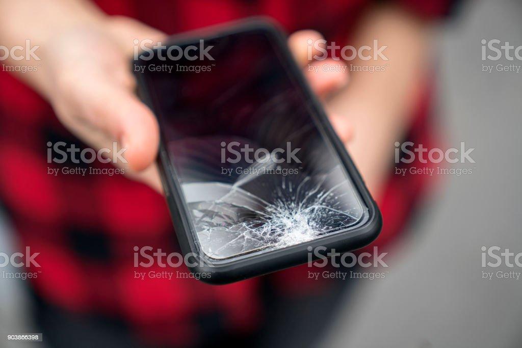 Gebroken telefoon in een vrouwelijke hand foto