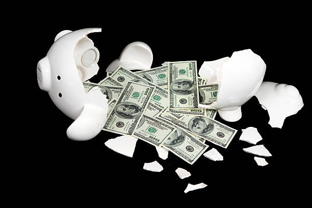 broken piggy bank and one hundred dollar bills - money black background stock photos and pictures
