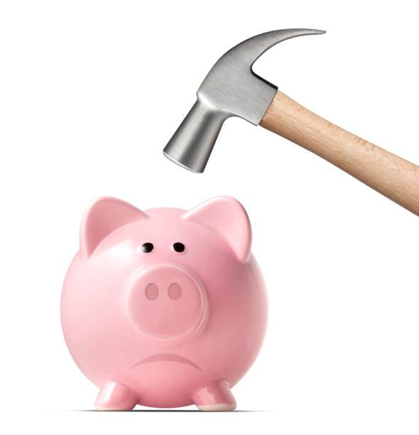 Broken piggy bank by hammer on white background stock photo