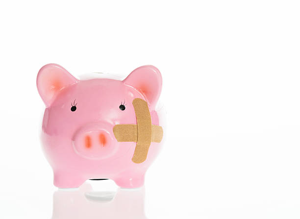 Broken piggy bank with band aids stock photo