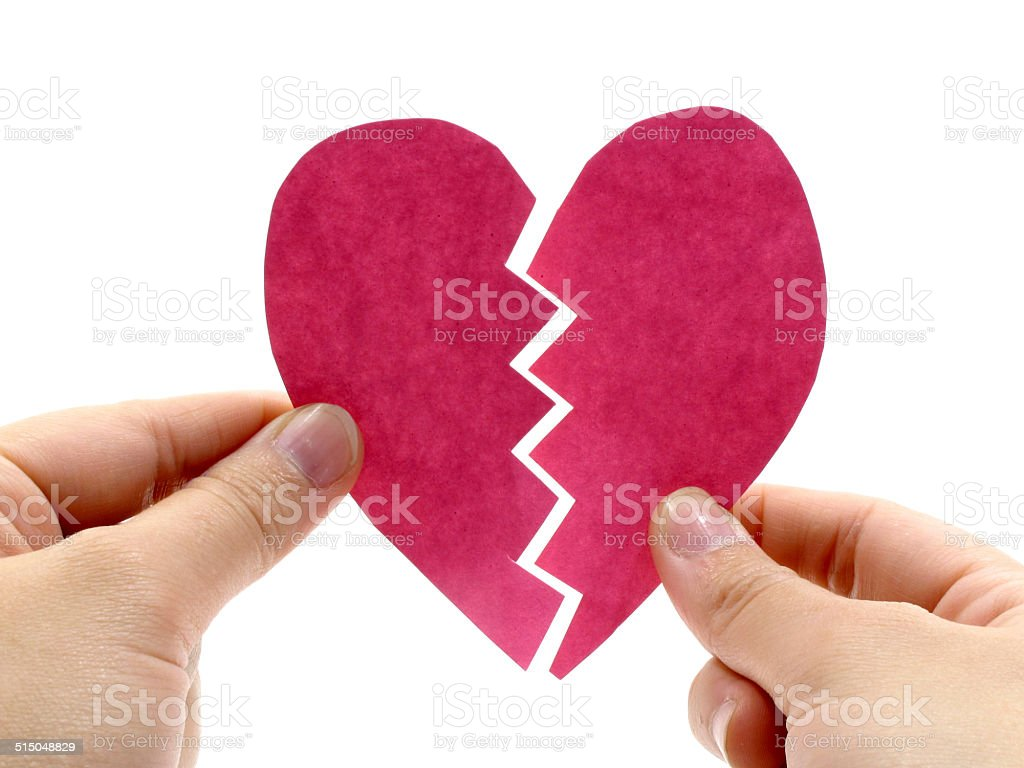 Broken pink heart on hand stock photo