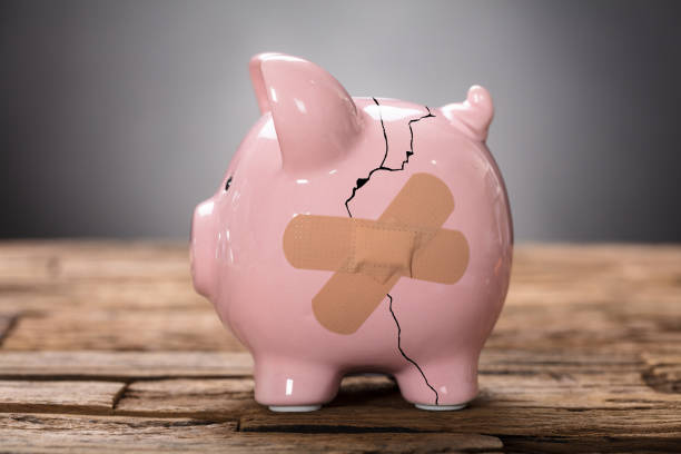 Broken Pink Piggybank With Bandage stock photo