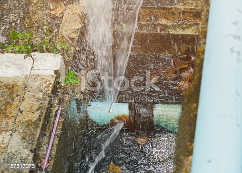 istock broken pipe in hole ditch at roadside and water Motion 1157517073