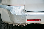 Broken plastic rear end bumper on the silver van glued with duct tape