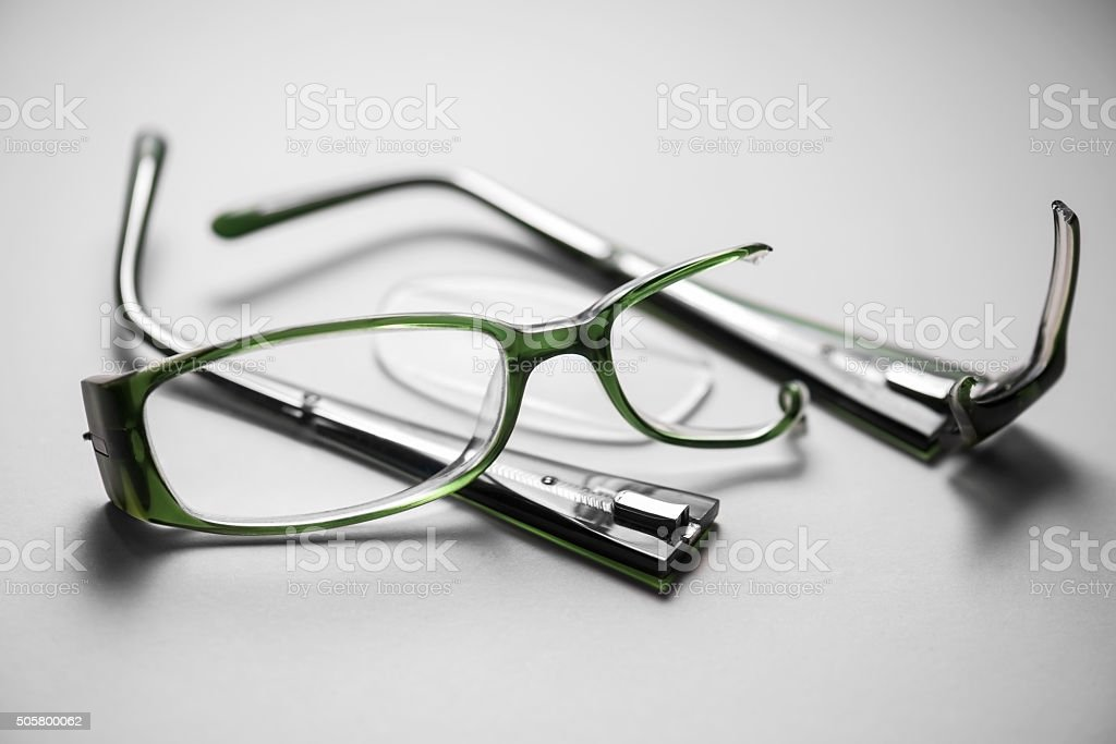 Broken plastic spectacles on a white background with strong shad stock photo