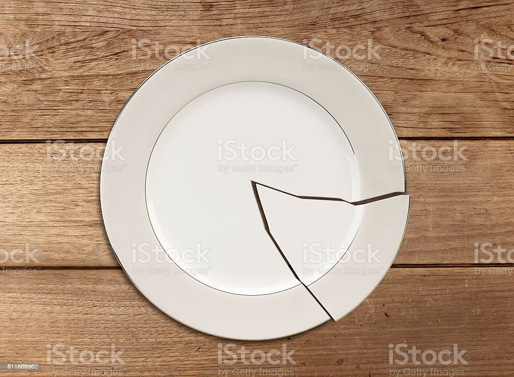Broken plate on wood table stock photo