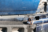 istock Broken rear light and bumper in crash accident on damaged blue car with dented sheet selective focus 891559896