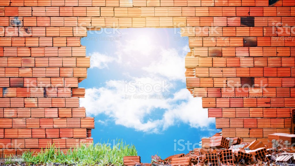 Broken red brick wall with a big hole in the middle and blue sky,...